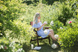 young woman is resting in the garden on a chair with a cup of tea