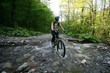 Girl on a bike crosses a small river