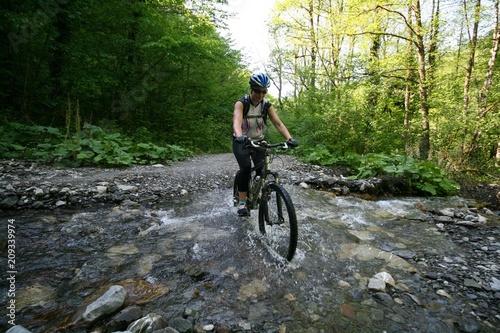 Foto op Aluminium Fietsen Girl on a bike crosses a small river