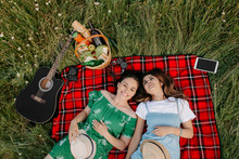 Two Cheerful Young Fashionable Women Lying Down On The Picnic Blanket And Relaxing.