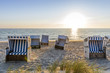 Germany, Schleswig-Holstein, Sylt, beach and empty hooded beach chairs at sunset