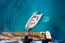 Inflatable Boat In The Sea In Bright Colorful Turquoise Water Is Tied To The Wooden Deck Of The Yacht, Top View.