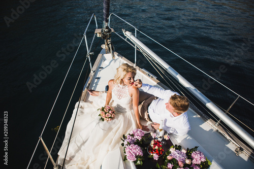 Beautiful stylish bride and groom on the luxury yacht traveling together on a warm summer day