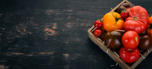 Assortment Of Tomatoes In A Wooden Box. Fresh Vegetables. On A Black Wooden Background. Top View. Copy Space.