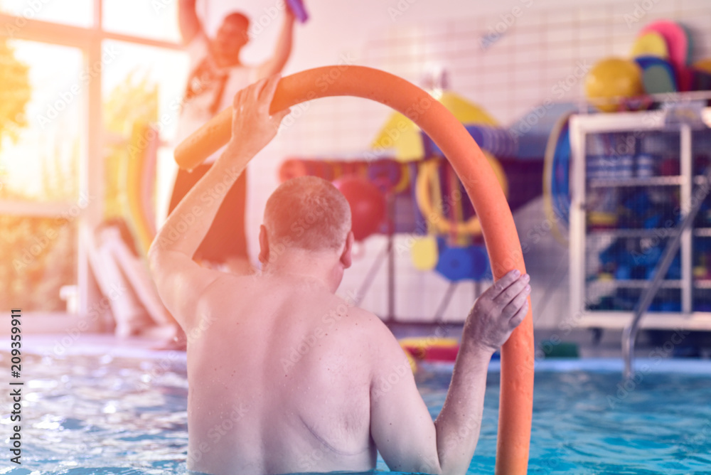 Fototapeta Group or young and senior people in aquarobic fitness swimming pool exercising