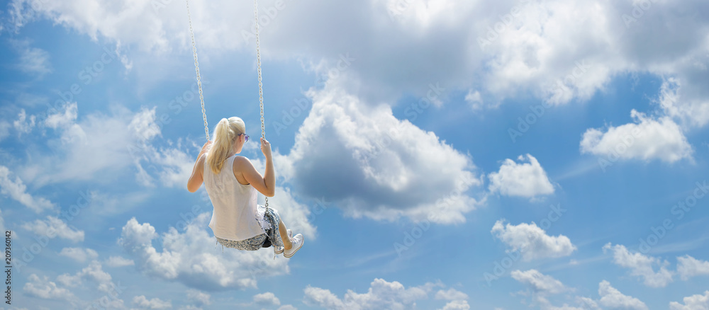 Fototapety, obrazy: Blonde girl with ponytail flying high among the white clouds on a swing