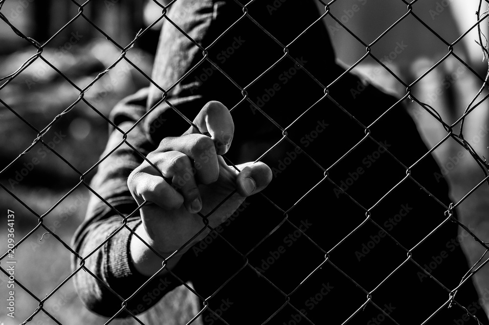 Fototapeta Young unidentifiable teenage boy holding the wired garden at the correctional institute in black and white, conceptual image of juvenile delinquency, focus on the boys hand.