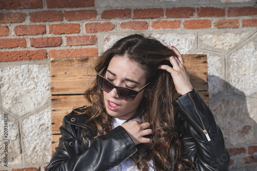 Fotografía  beautiful long-haired woman playing with sunglasses