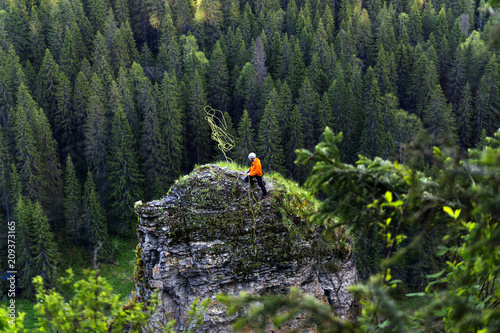 Poster  climber throws a rope, preparing to descend from the top of a steep cliff agains