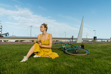 Woman Sitting On Grass With Bicycle