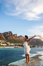 A Beautiful Young Black Woman With Outstretched Arms Stands On The Beach In Camps Bay, Cape Town, South  Africa