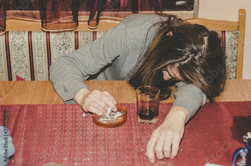 Fotografia  Drunk housewife drinking alcohol drink and smoking cigarette in her home on the