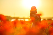 Woman In A Field With Poppies At Sunset, In The Sun, Soft Focus