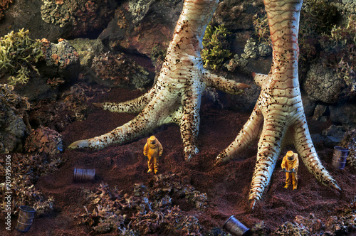 Photo of giant chicken feet and toy people near them Canvas-taulu