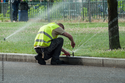 Photo Stands Olive transportation company employee adjusting automatic sprinklers on tramway line