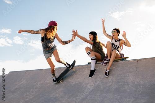 Valokuvatapetti Skater girl riding skateboard at skate park with friends