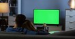 Rear of the romantic couple hugging on the couch while watching TV with green screen and changing channels late at night in the living room. Indoor