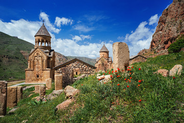 Noravank monastery complex built on ledge of narrow gorge. Sunny day in mountains. Tourist and historical place. Travelling to Armenia in summer.