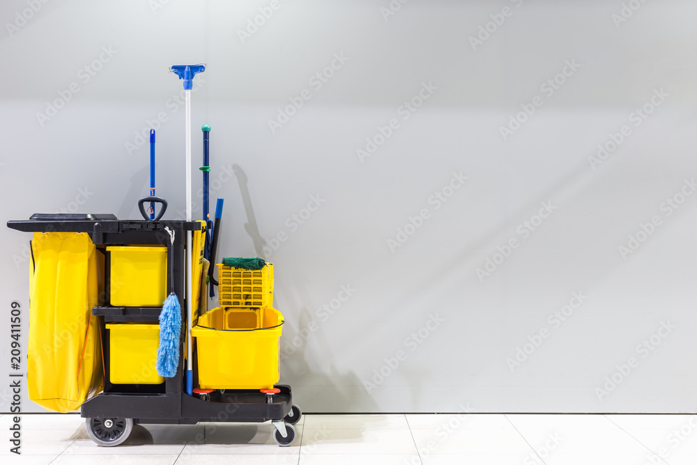 Fototapeta Mop bucket and set of cleaning equipment and sign of men toilet on the wall in the airport