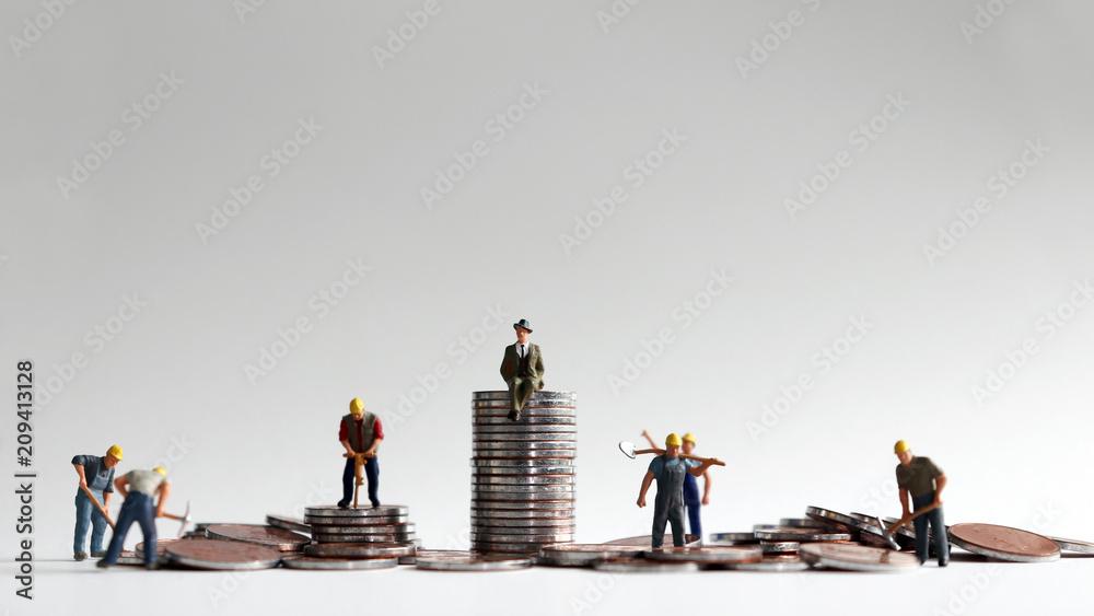 Fototapeta The concept of a growing economic gap. Pileofcoinsandminiaturepeople.