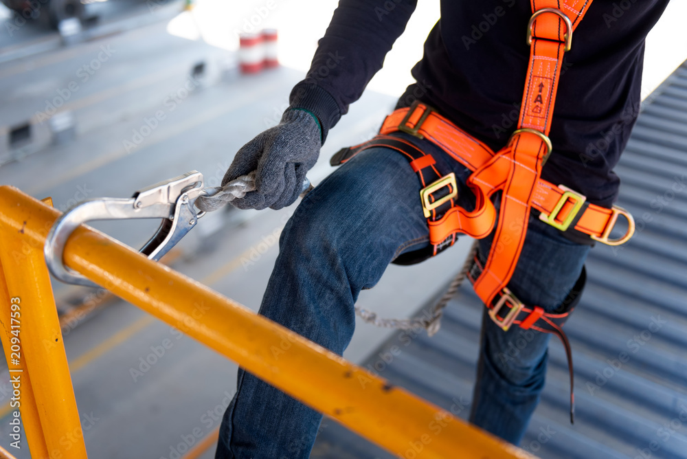Fototapety, obrazy: Construction worker use safety harness and safety line working on a new construction site project.