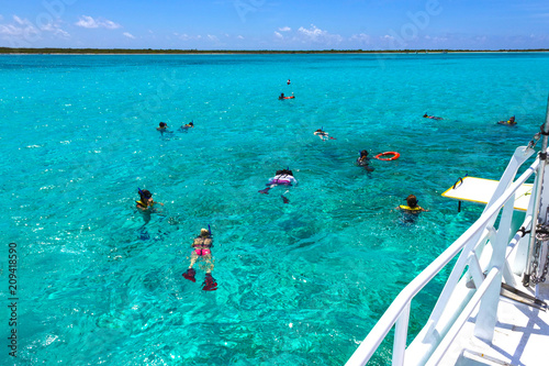 plakat Cozumel, Mexico - Group of friends relaxing together on a party boat tour of the Carribean Sea