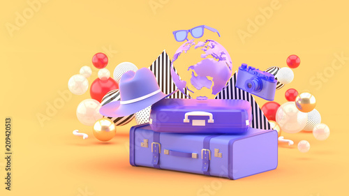 Foto  A suitcase under the globe surrounded by a camera and hat on an orange background