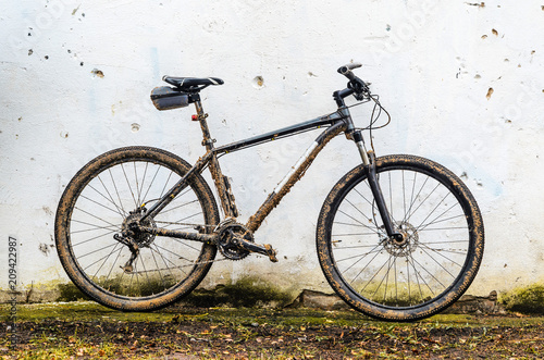 Dirty Mountain Bike Covered with Mud After Riding in Bad Weather Stands. Grey 29er Hardtail Bike on White Wall Background