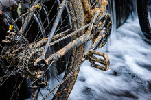 Dirty Mountain Bike Stands In A Creek Against The Small Waterfall. Dirty Chain Drive Mountain Bike Close-up. Cleaning A Bicycle Concept