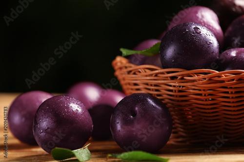 Ripe juicy plums on table