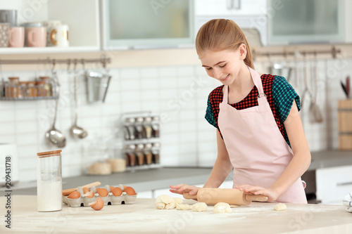 Poster Cuisine Teenage girl rolling dough on table in kitchen