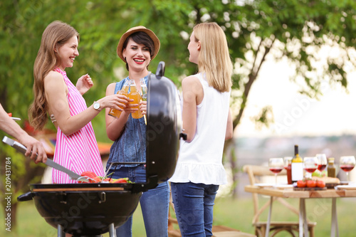 Young women having barbecue with modern grill outdoors Canvas Print