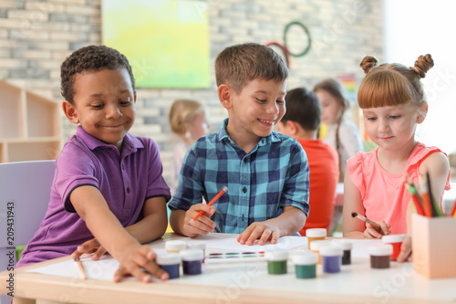 Cute little children painting at table indoors. Learning by playing