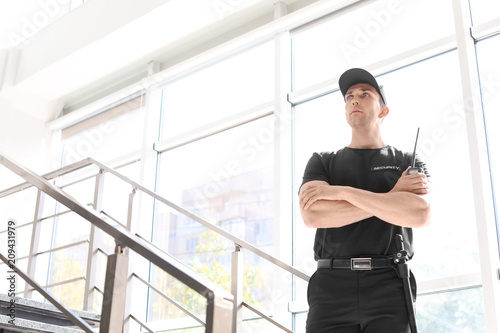 Photographie Male security guard with portable radio transmitter indoors