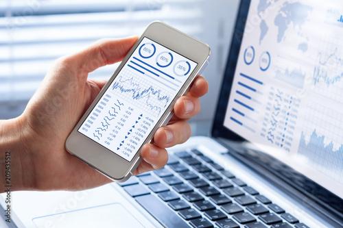 Fotografía  Investor analyzing stock market with financial dashboard on smartphone, computer