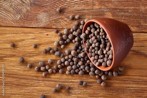 Fotografia Overturned clay bowl with dried allspice berries on rustic wooden background, close-up, macro, selective focus
