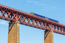 Forth Bridge, Railway Bridge Over Firth Of Forth Near Queensferry In Scotland With Train Passing The Bridge