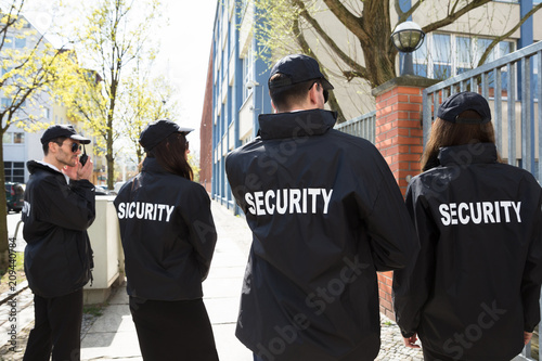 Security Guards Standing Outside Building Wallpaper Mural