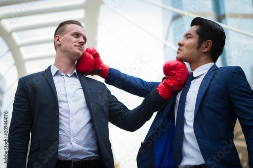 caucasian businessman wear black suit and asian businessman man wear blue suit with red boxing gloves fighting by uppercut to chin Poster