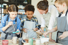 Several Schoolkids And Teacher In Aprons Choosing Paints To Paint Up Clay Mugs They Made By Themselves