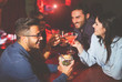 canvas print picture - Happy friends drinking and toasting cocktails in a jazz bar - Young people cheering and laughing together in a club at night - Friendship, lifestyle, nightlife concept