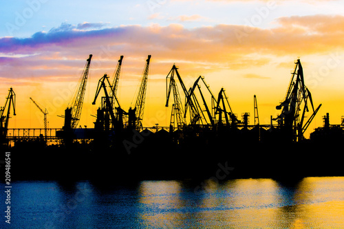 Foto op Plexiglas Poort Silhouette of a crane. Cranes at the port. Silhouette of harbor at sunset. Sea port. Sunset at the port.