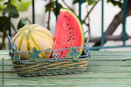 Foto  Seasonal fresh fruits, watermelon and rockmelon in basket on garden table