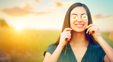 Beauty Joyful Girl With Daisy Flowers On Her Eyes Enjoying Nature And Laughing On Summer Field. Beautiful Young Woman Having Fun