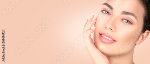 Beautiful brunette girl touching her face. Perfect fresh skin. Spa beauty portrait. Youth and skincare concept, cleansing