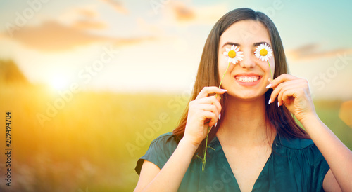 Foto  Beauty joyful girl with daisy flowers on her eyes enjoying nature and laughing on summer field