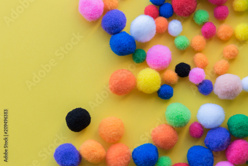 Fotografia Multi-colored  pom-poms in assorted sizes on solid yellow background flat lay ar