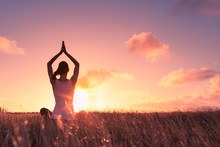 Peace And Serenity. Female Meditation Outdoors In A Open Field At Sunset.