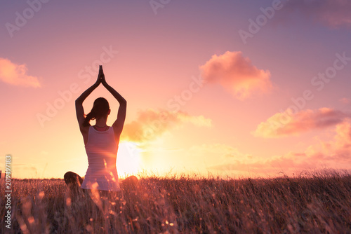 Obraz Peace and serenity. Female meditation outdoors in a open field at sunset.  - fototapety do salonu