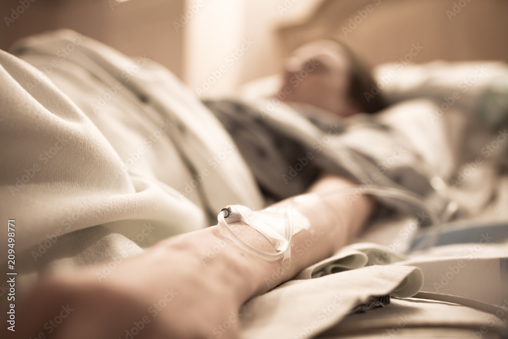 Fototapeta Unrecognizable sick woman lying in hospital bed.